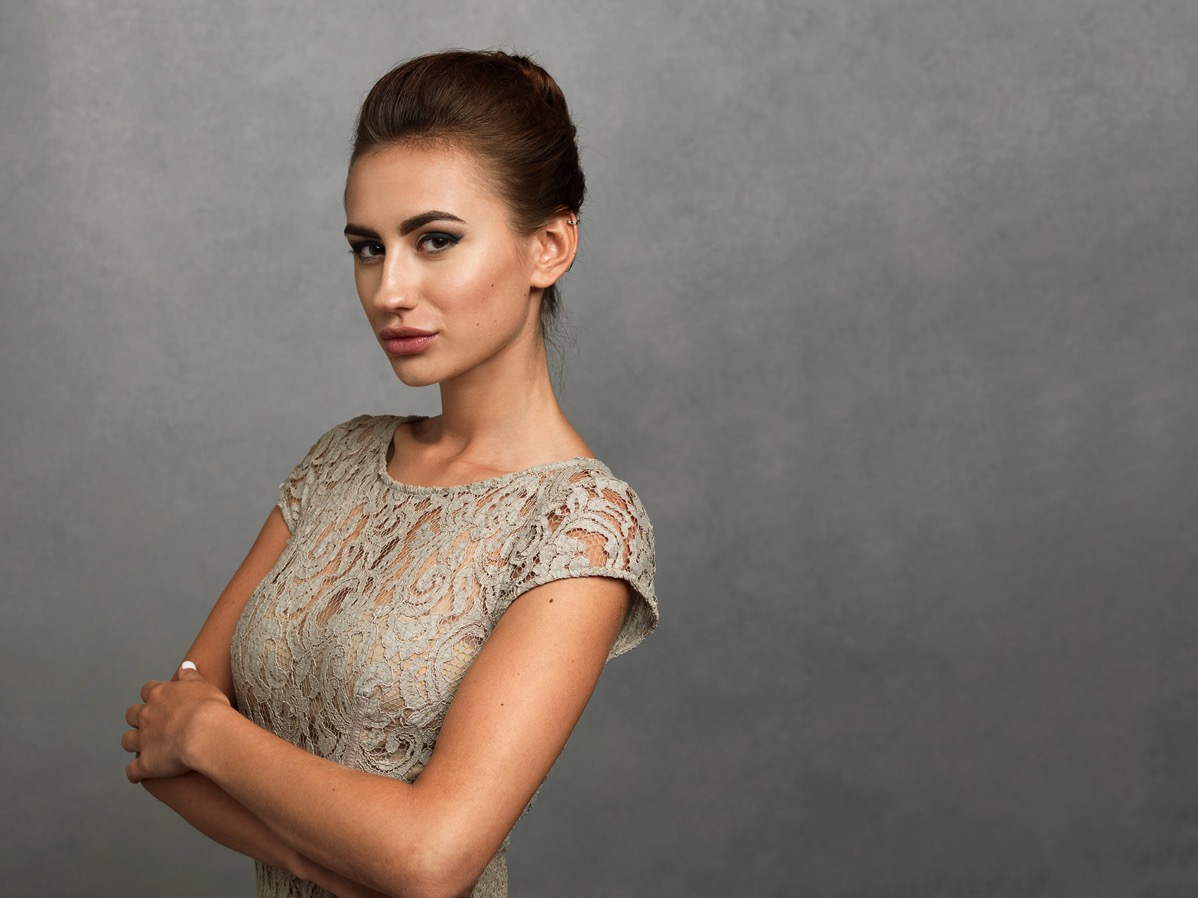 beautiful young woman with great jawline and cheekbones crossing her arms wearing a classic textured dress
